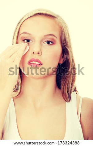 Teen woman removing makeup with cleansing pad , isolated on white - stock photo