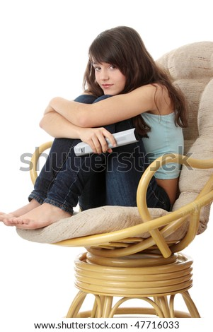 Teen woman watching TV with remote control while sitting on armchair view from TV