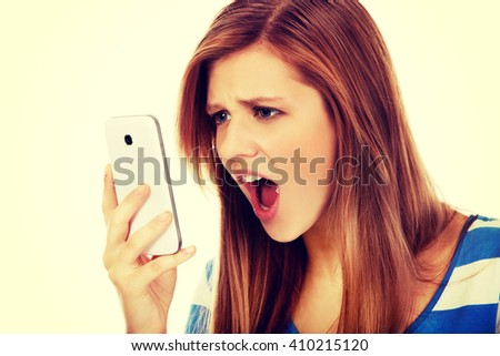 Teenage angry woman screaming into the phone - stock photo