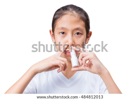 Teenage asian girl using nasal spray with one hand holding the spray bottle to her nose's left side and index finger of the other hand pressing on her nose's right side to block the air flow, on white
