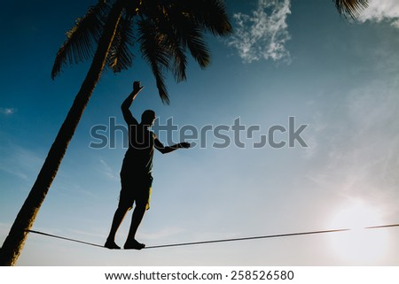 teenage balancing on slackline with sky view on the beach silhouette - stock photo