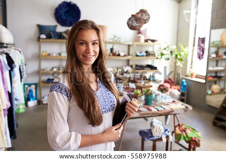 Teenage boutique assistant holding tablet computer in shop. Young Female Business Owner Clothes Shop Stock Photo 558977833