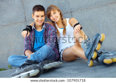 Teenage boy and girl having a rest after roller-skating - stock photo