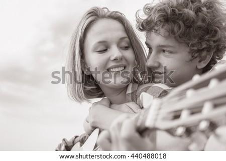 Teenage boy and girl  play guitar outdoors - stock photo