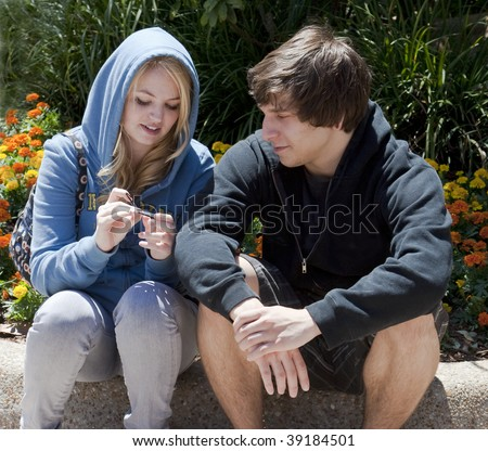 Teenage boy and girl, 18-years-old, sitting and talking on a curb with flowers behind them.  Both are wearing sweatshirts and are looking at something the girl is holding. - stock photo