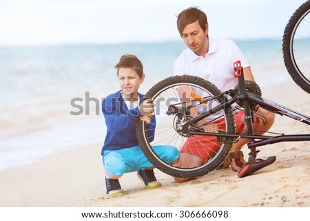Teenage boy and his father repairing bicycle outdoors at summer - stock photo