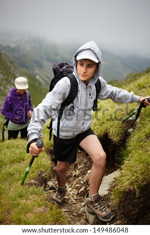 Teenage boy and his mother hiking into the Romanian Carpathians mountains - stock photo