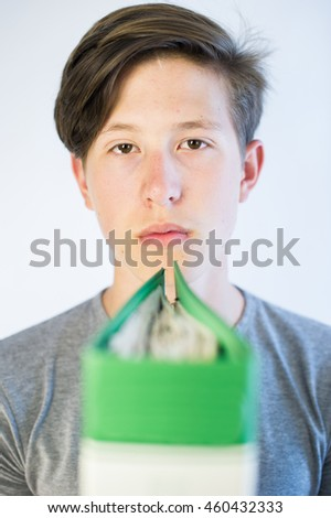 Teenage boy behind a green school binder.