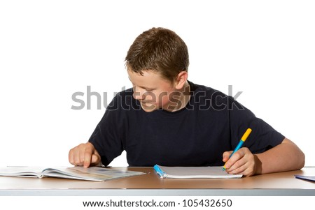 Teenage boy concentrating on his studies as he makes notes in a book from the information he is researching in his textbook - stock photo