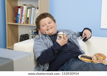 Teenage Boy Eating Donut And Watching Television - stock photo