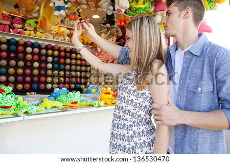 Teenage boy helping his girlfriend aim while playing a darts game at an amusement park arcade with prices and toys around them. Side view. - stock photo