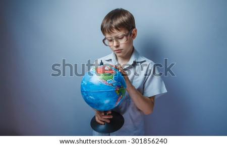 Teenage boy holding a globe of the Earth with glasses on a blue background photo studio for the site is formed