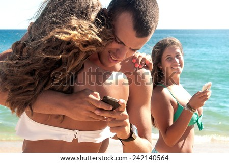 Teenage boy holding girl friend and texting another girl - stock photo