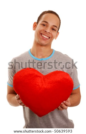 Teenage boy holding heart shaped pillow