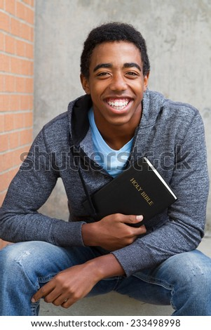 Teenage boy holding his Bible at school - stock photo