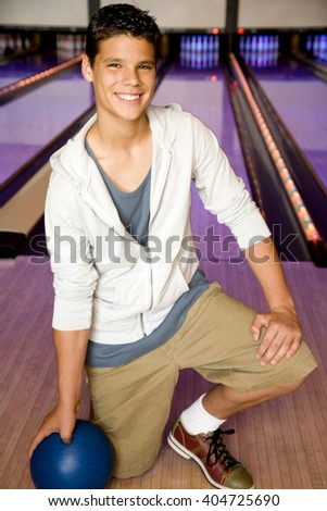 Teenage boy in a bowling alley, holding a blue bowling ball - stock photo