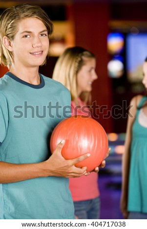 Teenage boy in a bowling alley, two girls in the background