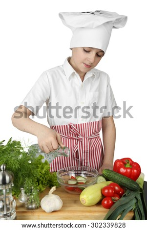 Teenage boy in cook chef hat and apron adds condiment to salad bowl on cutting board surrounded by vegetables and spices isolated on white background - stock photo