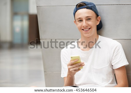 Teenage boy in street wear looking and smiling at the camera with cheerful expression while texting his friends via social networks using mobile phone, sitting against urban landscape background - stock photo
