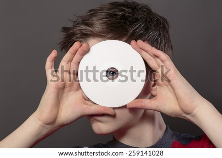 teenage boy is looking through the hole of a white disc, with gray background for fast isolating - stock photo