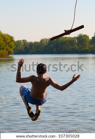 Teenage boy jumping in the river from the swinging rope on sunny summer day. - stock photo