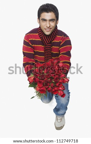 Teenage boy kneeling with a bouquet of flowers