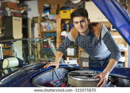 teenage boy leaning over the engine of a classic car in garage looking at camera - stock photo