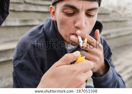 teenage boy lighting cigarette in urban setting - stock photo