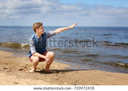 Teenage boy on beach squatting with hand points to the sea
