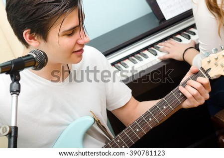 Teenage boy playing electric guitar and singing while girl plays on piano.