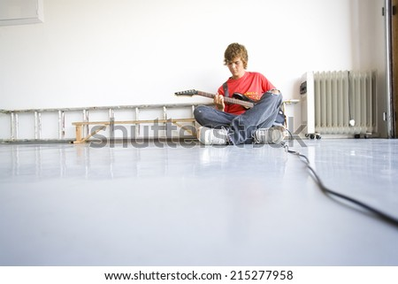 Teenage boy (16-18) playing electric guitar, sitting cross-legged on ground - stock photo