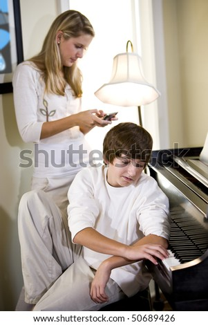 Teenage boy playing piano with sister texting in background - stock photo