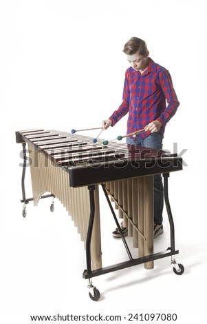 teenage boy playing the marimba in studio against white background - stock photo