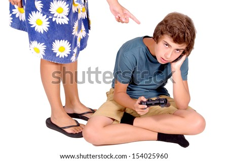 teenage boy playing video games while mother argues - stock photo