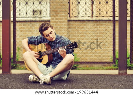 Teenage boy plays an acoustic guitar - stock photo