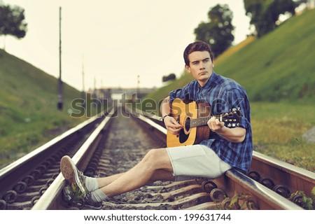 Teenage boy plays an acoustic guitar - stock photo
