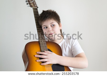 Teenage Boy plays an acoustic guitar while relaxing on a patio chair.