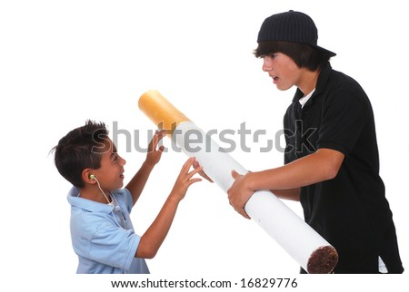 Teenage boy pushes a large cigarette on his younger brother - stock photo