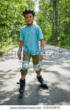 Teenage boy roller-skates on walkway in park - stock photo