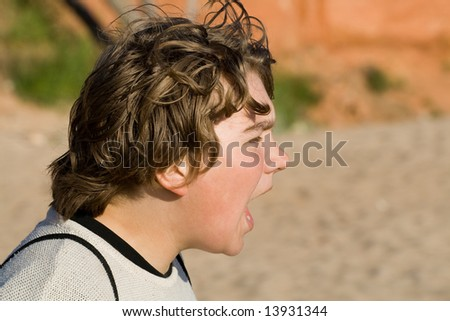Teenage boy shouting. Beach sand and red sanstouns in background - stock photo