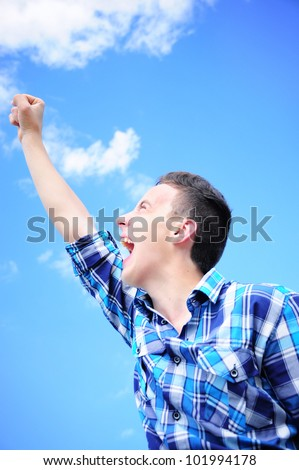 Teenage boy shouting victorious with his arm raised - stock photo