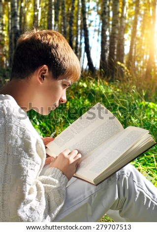 Teenage boy sit in autumn forest with a book