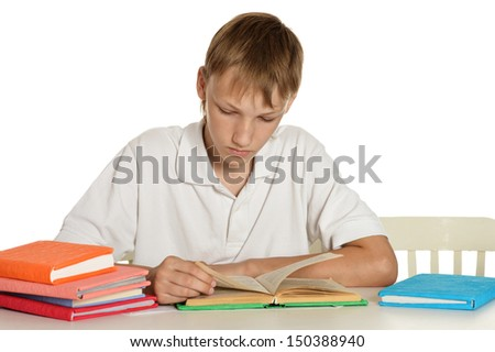 Teenage boy sitting at a desk with books - stock photo