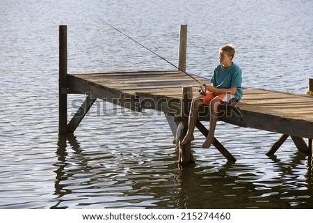 Teenage boy (13-15) sitting at edge of jetty, fishing in lake - stock photo