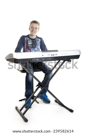 teenage boy sitting at keyboard playing music - stock photo