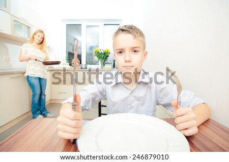 Teenage boy sitting at the table waiting for dinner and playing with forks while his mother cooking in the kitchen - stock photo