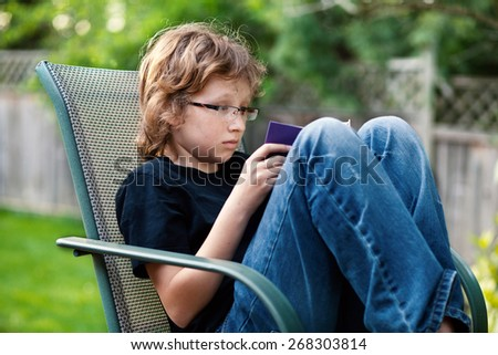 Teenage boy sitting on a chair outside reading a book.
