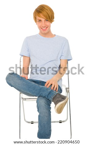 teenage boy sitting on chair - stock photo