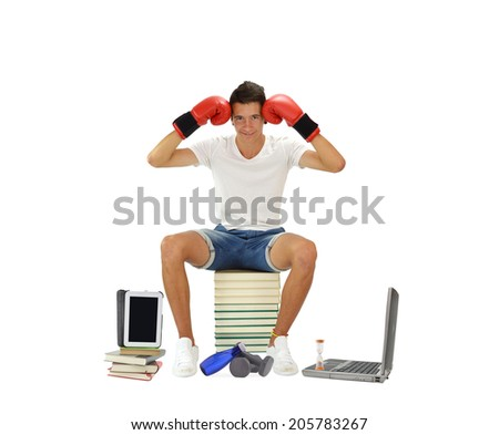 Teenage Boy sitting on stack of books with laptop, hourglass, digital tablet, weights, and water with his head between red boxing gloves looking at the camera