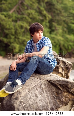 Teenage boy sitting on the rock at the ocean bay. - stock photo